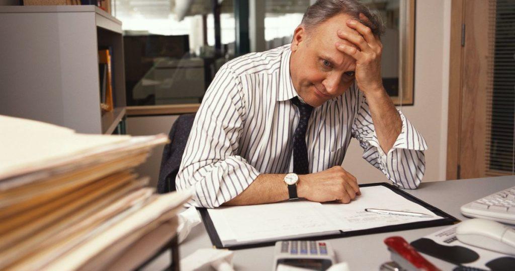 Foto di un uomo seduto ad una scrivania piena di fogli che si tiene la testa con la mano sinistra, ha un'espressione afflitta