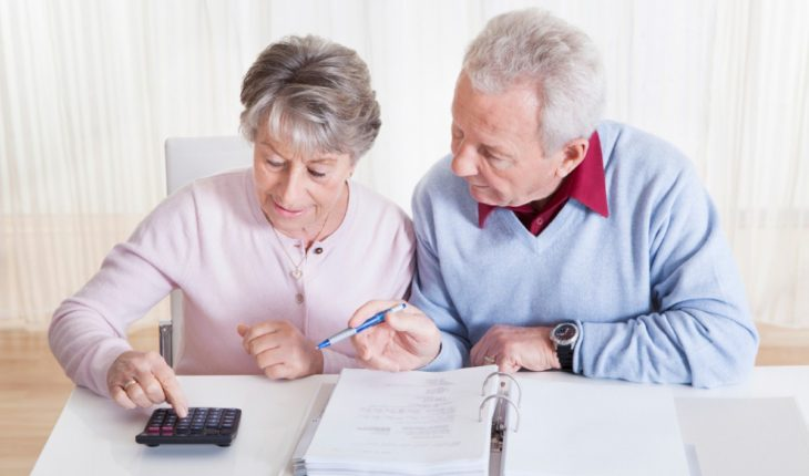 una coppia di persone anziane sedute ad un tavolo intente a fare calcoli e conti