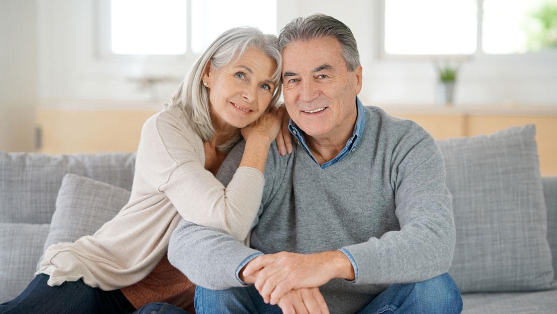 una coppia di anziani seduti su un divano grigio