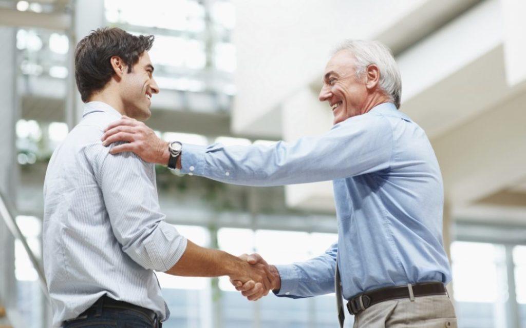 un uomo anziano stringe la mano ad un uomo giovane