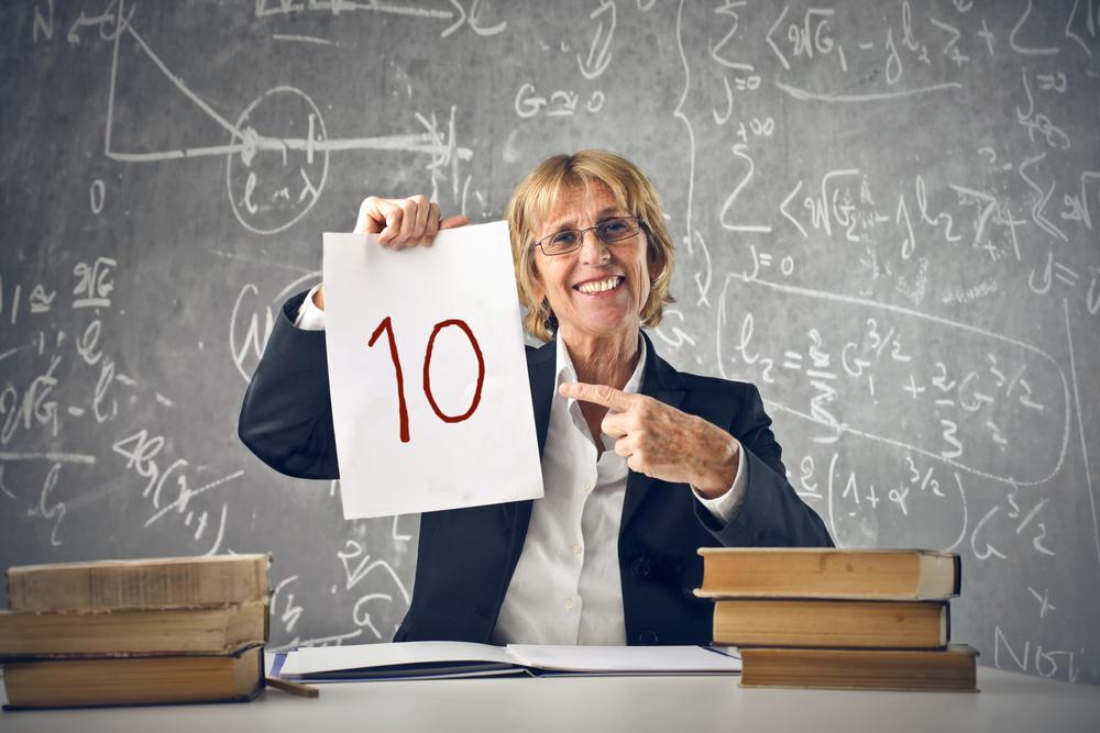 professoressa seduta alla scrivania che mostra un foglio su cui è scritto il numero 10 in rosso