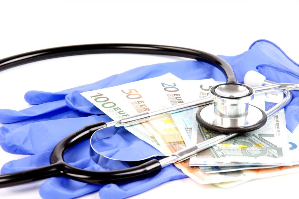 stetoscopio, guanti in lattice e banconote poggiate su un tavolo bianco