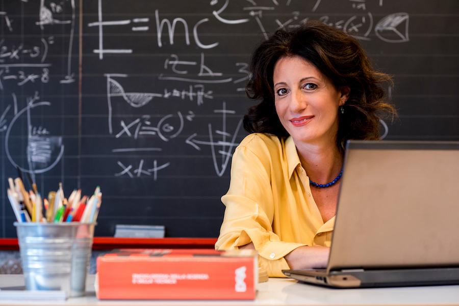 Professoressa seduta in cattedra, alle sue spalle una lavagna piena di equazioni matematiche